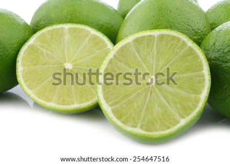 lime fruits and a cut one on a white background - stock photo