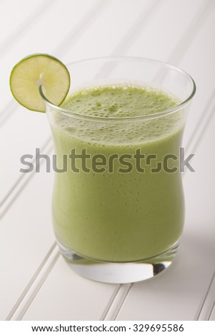 lime green pineapple smoothie on white wood