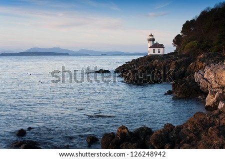 Lime Kiln Lighthouse. Situated in the northwest corner of Washington State, the San Juan Islands are breathtaking gems on a gentle sea that attract numerous visitors and adventurers each summer. - stock photo