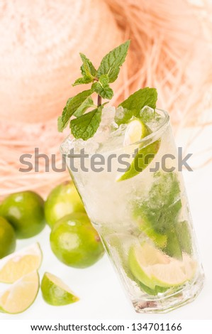 Lime Mojito cocktail close up with a straw hat background - stock photo