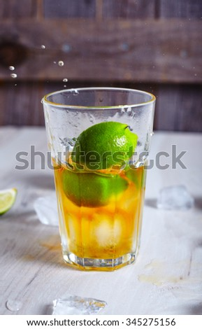 Lime that dropped into glass with rum and ice with limes around it. Proccess of making Cuba-Libre cocktail or Rum-Cola on wooden background