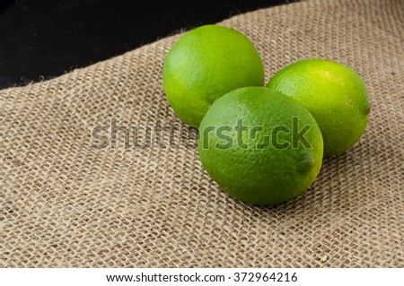 Limes on a jute table cloth black background - stock photo