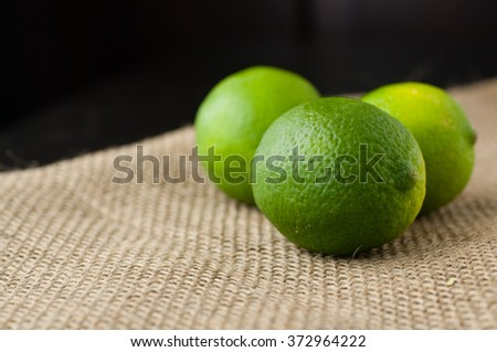 Limes on a jute table cloth black background