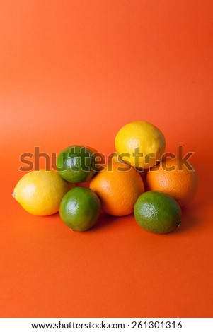 Limes, oranges, lemons on a coloured background - stock photo