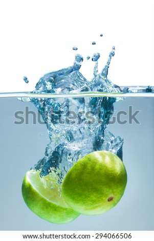limes splashing into water on white background - stock photo