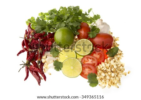 Limes, tomatoes, cilantro hot peppers and garlic, all possible ingredients for a posole. - stock photo