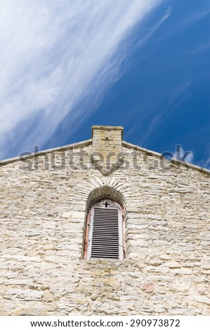 Limestone facade of ancient church with window shutter and cross shape in wall - stock photo