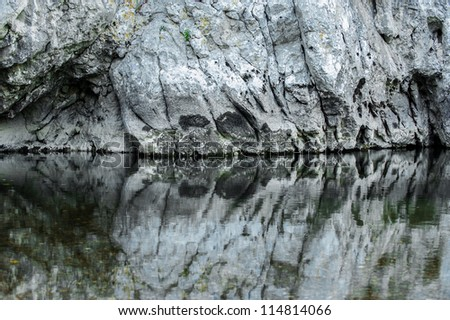 Limestone rock reflection in mountain river - stock photo