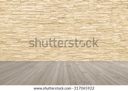 Limestone rock tile wall backdrop in yellow cream brown color tone with wooden floor in light sepia colour: Grunge vintage style room with rustic stone wall pattern background and wood flooring     - stock photo
