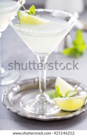 Limonade martini cocktail garnished with lime and mint - stock photo