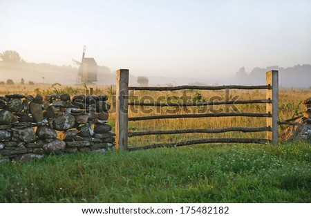 Limstone fence with a gate during sunrise on a misty landscape.TN - stock photo