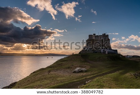 Lindisfarne Castle late afternoon / The warm glow of the suns rays shine from behind a cloud at Lindisfarne Castle