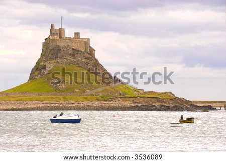 Lindisfarne Castle with boats in Holy Island harbour