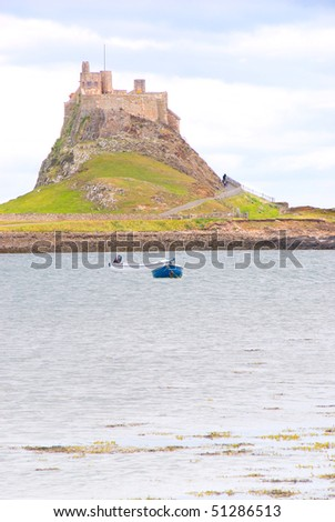 Lindisfarne Castle with boats in Holy Island harbour - stock photo