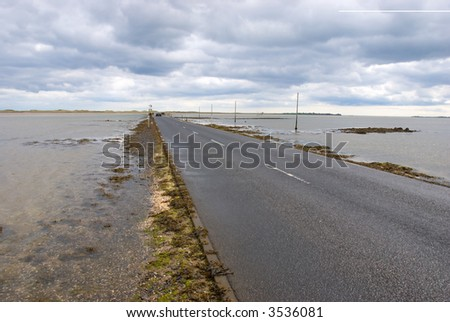 Lindisfarne causeway minutes before being submerged - stock photo