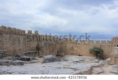 Lindos, Rhodes, Greece - September 21, 2015: Tourists at the top of Lindos ancient Acropolis ruins. - stock photo