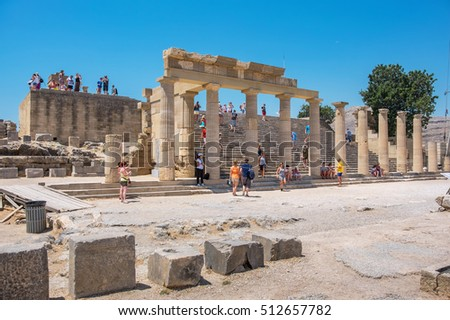 LINDOS, RHODES ISLAND, GREECE - JULY 9, 2015: Tourists visiting in the Acropolis of Lindos. In the center Staircase of the Propylaea