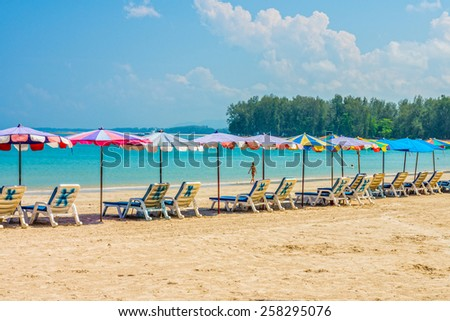Line of beach umbrellas and sunbathe seats on Phuket sand beach in Southern Thailand - stock photo