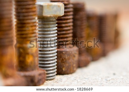 line of bolts on concrete - stock photo