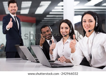 Line of call centre employees are working on computers. They are smiling and looking at the camera. - stock photo