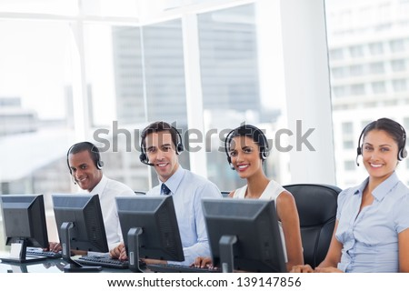 Line of call centre employees smiling and working on computers  stock