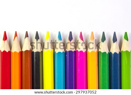 Line of colored pencils isolated on white background close up