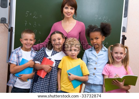 Line of cute schoolchildren looking at camera with their teacher near by - stock photo