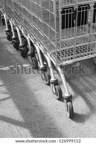 Line of empty supermarket trolleys at local store. - stock photo