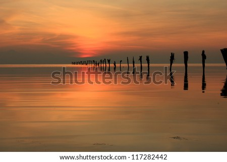 Line of fence posts at the Great Salt Lake at dusk, Utah, USA. - stock photo