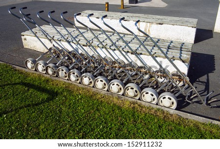 line of golfing caddy trollys beside golf course - stock photo