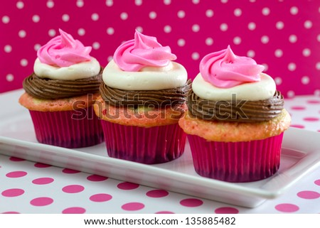 Line of 3 neapolitan frosted cupcakes on long white plate with pink polka dots - stock photo
