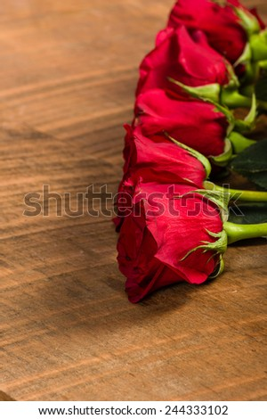 Line of red roses on a rough wooden table - stock photo