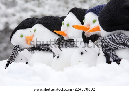 Line of snowmen with carol singing books, hats and scarfs in the snow for winter