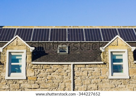 Line of solar panels on the roof of a stone house in Scotland - stock photo