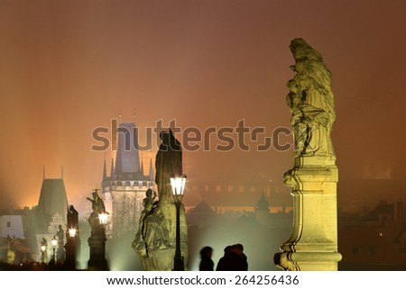 Line of street lamps and sculptures along Charles bridge in foggy night, Prague, Czech Republic - stock photo