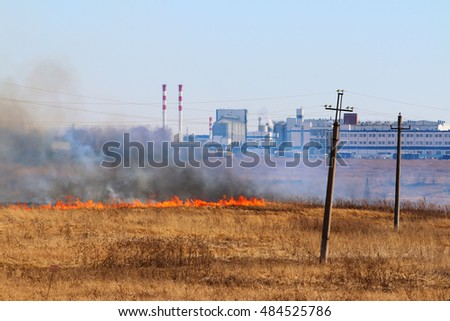 Line of the fire coming to industrial city district - burning meadow grass