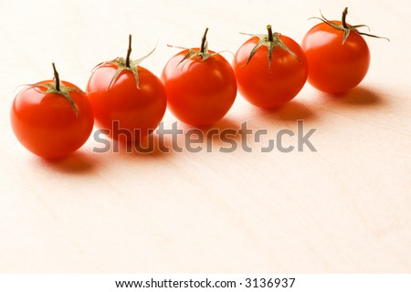 Line of tomatoes on wooden plate