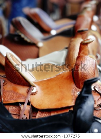 Line of Western Saddles for Sale (shallow focus). - stock photo