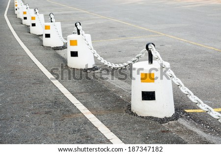Line of white cement pole and iron chain on street