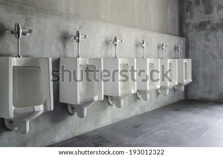 Line of white porcelain urinals in public toilets - stock photo