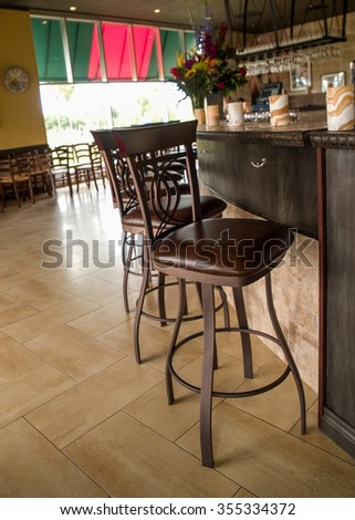 Line up of leather and wood bar stools at an Italian restaurant.