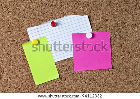 Lined blank notebook paper, green paper and pink paper notes attached to brown corkboard with yellow red and white pins - stock photo