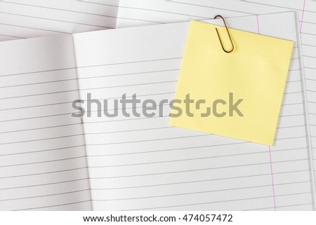 Lined exercise books with blank yellow sticky note