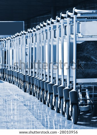 Lined up trolleys at airport - stock photo