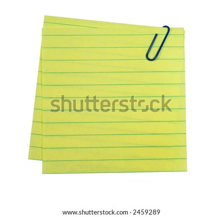 Lined yellow paper attached with a blue paper clip. - stock photo