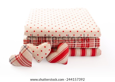 Linen fabric with red polka dots, plaid and stripes for needlework stacked in pile isolated. Heart made of cloth.  - stock photo