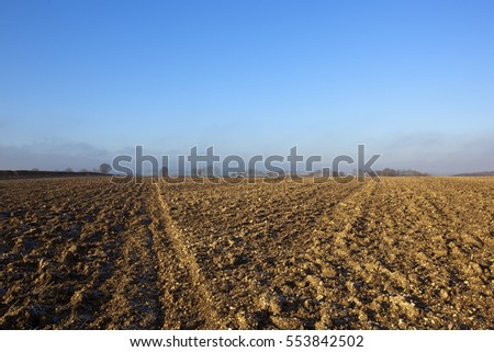 lines and patterns in chalky plow soil in a yorkshire wolds landscape with trees and hedgerows in the distance under a blue cloudy sky in winter