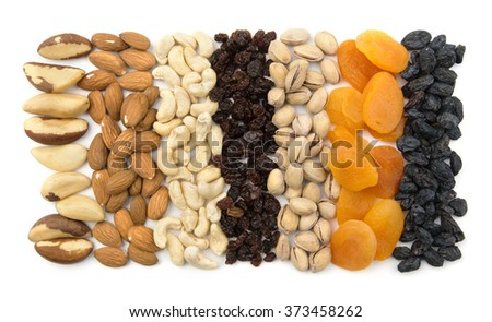 Lines of nuts, raisins and dried apricots on white background