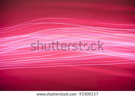 Lines of pink light streaking across a red background - stock photo
