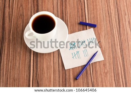 Lines on a napkin and cup of coffee - stock photo